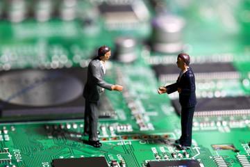 Miniature businessmen circuit board. Miniature business figures standing on a circuit board.