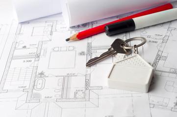 House keys on a house plan blueprint concept for new house desig