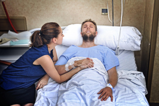 couple at hospital room man in bed and woman holding hand caring