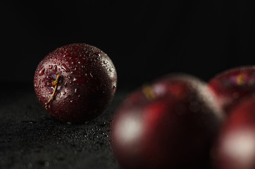 Low key shot of Plums on a black, smooth and wet surface