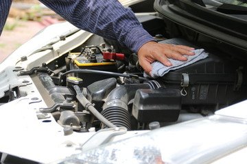 Man is cleaning his car engine with a rag.