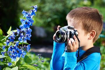 Little boy with retro camera shooting macro flowers
