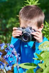 Little boy with retro SLR camera shooting macro flowers