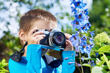 Little boy with retro SLR camera shooting macro flowers