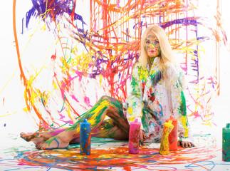 Blonde Frau inmitten von Farben und Tuben