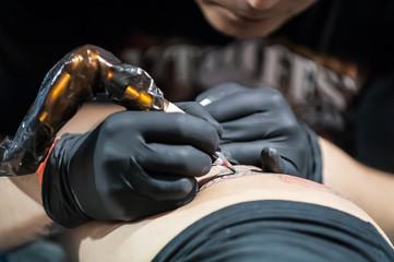 Tattoo Making. Tattooist with protective gloves creates a tattoo.  Closeup