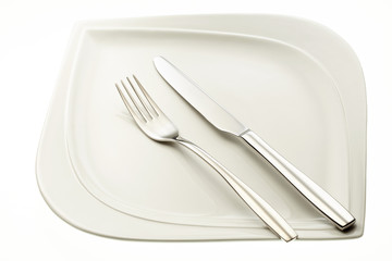 Stainless fork and knife on plate