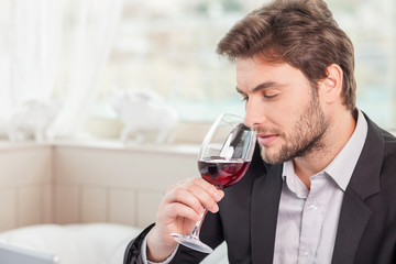 Young well-dressed man is relaxing in restaurant