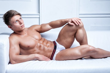 muscular sexy young shirtless man lying on the sofa
