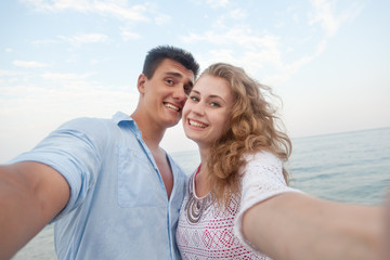 young couple beach doing selfie on the beach