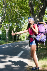 cheerful young woman backpacker hitchhiking on a roadside in summer vacation