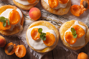 Apricot cakes with cream and mint close-up horizontal top view