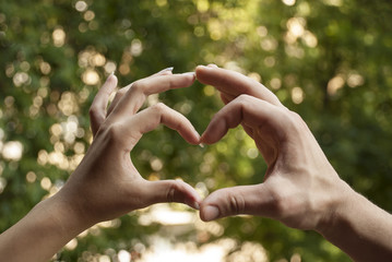 Female and male hand forming sign of heart