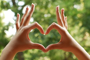 Heart shape made by woman hands
