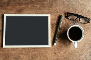 Blank blackboard and wooden pencil on old wooden background