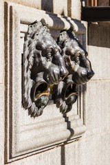 a sculpture of two lions iron to a mailbox in the city of Avila, Spain