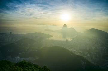 Scenic sunrise in Rio de Janeiro Brazil glows golden over Guanabara Bay with a skyline silhouette of Sugarloaf Mountain