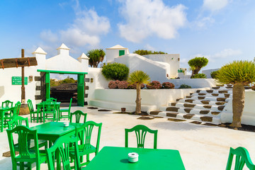 Green tables with chairs in typical Canarian style village, El Campesino Monumento, Lanzarote island, Spain