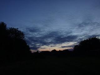 Догорающий розовый закат и синее небо с перистыми облаками поздним летним вечером
