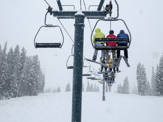 Three skiers on a chair lift in primary colors