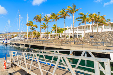 Palm trees in Caribbean style port for yacht boats, Puerto Calero, Lanzarote island, Spain