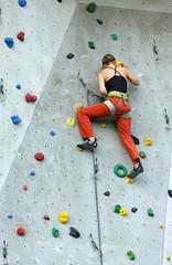 Frau klettert an Übungswand