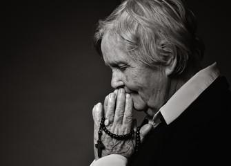 Praying senior woman.
