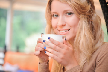 Pretty blond-haired woman with cup of coffee