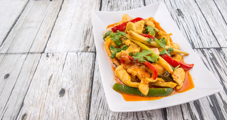 Malaysian traditional dish of Ayam Paprik or spicy stir fry chicken on white plate over wooden background