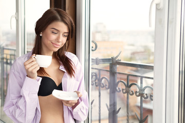 Young sexy woman wearing man's shirt and enjoying her morning co