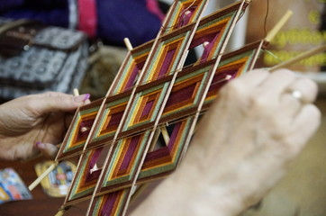 Photo of tibetian mandala hand weaving with thread on a wooden base