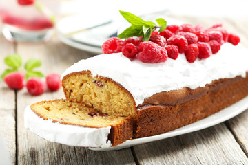 Raspberry cake on plate on grey wooden background