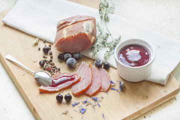 Smoked meat with currant sauce and spices on a wooden board