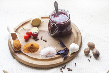 Cherry sauce, cherries and spices on a wooden board