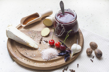 Cherry sauce with cheese brie, cherry and spice on wooden board