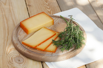 Sliced cheese on wooden board with dill and rosemary, selective focus