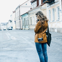 Beautiful girl with an old camera walks through the ancient streets