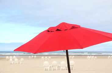 A red beach umbrella in the ocean sand at sea side.
