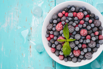 Frozen berries on a turquoise background with space for text, to