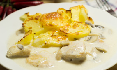 Chicken breast with mushroom sauce and browning potatoes with cheese