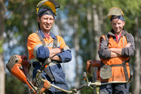 Happy garden workers with petrol string trimmers outdoors