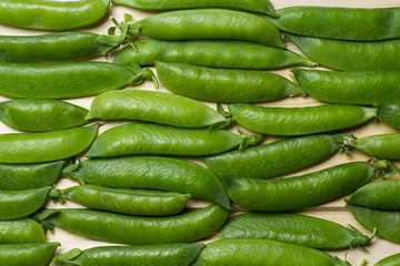 pea pods on a wooden surface