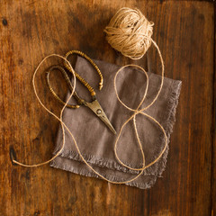 scissors lying on linen fabric with a rope on a wooden backgroun