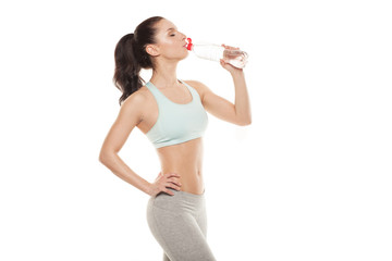 Sporty girl drinking water from a bottle after a workout, fitness training, isolated on white background