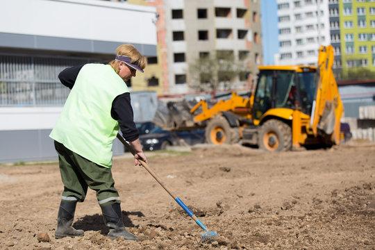 City landscaper preparing soil for grass planting