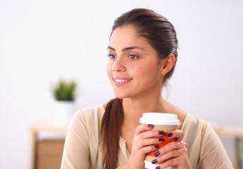 Beautiful  businesswoman enjoying coffee in bright office