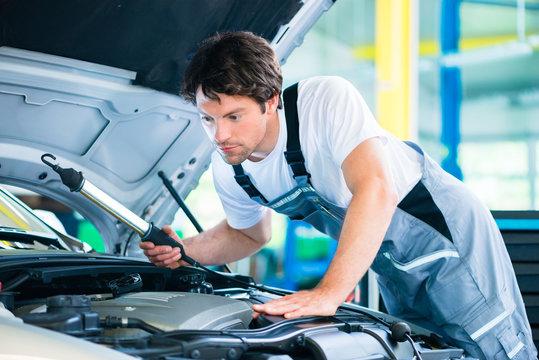 Mechaniker untersucht Auto Motor mit LED Licht in Kfz-Werkstatt