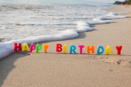 Happy birthday candles on a beach.