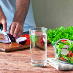 glass of clean water with a salad of fresh vegetables in the rustic kitchen. The concept of healthy lifestyle and diet. Close-up. Copy space. Free space for text