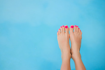 Photo sur Plexiglas Pedicure Bare feet over blue swimming pool water